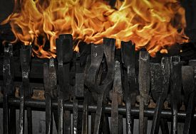 stock photo of tong  - smith tongs in the background of forging fire of an outbreak - JPG