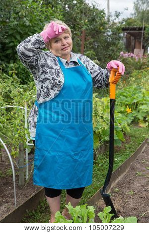 Senior tired woman digging on field