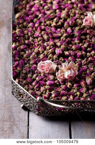 Dried roses and rose buds in a vintage tray