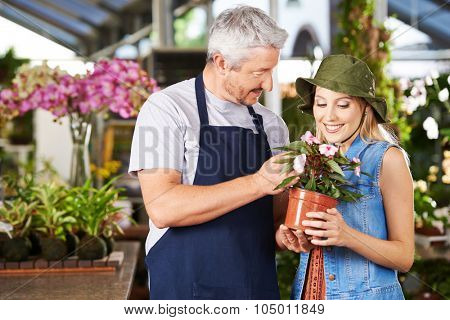 Florist talking to woman with impatiens flower in a nursery