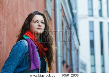 Street portrait of attractive brunette girl posing at city buildings architectural pattern backgroun