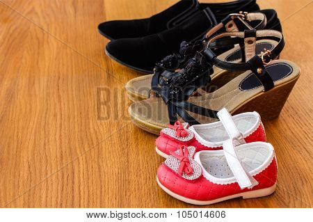 Three pairs of shoes: men, women and children.