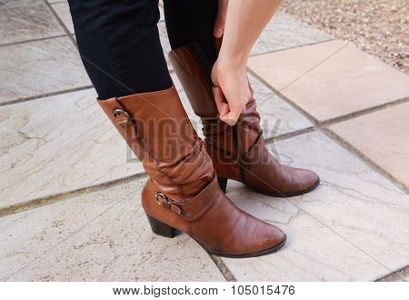 Young Woman Zipping Up Her Fashionable Leather Boots