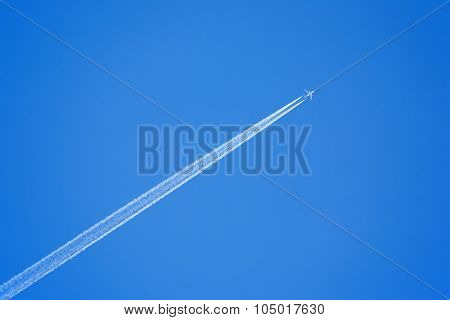 Passenger jet flying in clear blue sky, leaving white trail