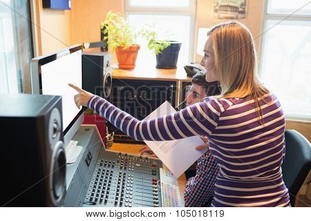 Female employee explaining male radio host while pointing on monitor at desk in studio