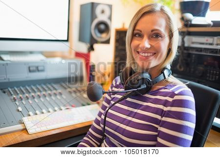 Portrait of happy young radio host sitting on chair in studio