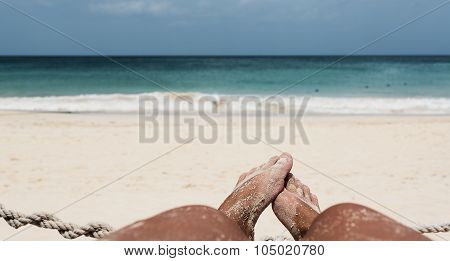 Feet on the beach with wide sea horizon, focus on feet