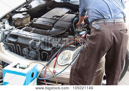 Mechanic With Manometer Filling Gas Into Auto Vehicle Air-condition Compresser