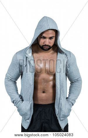 Muscular man in hooded jumper on white background