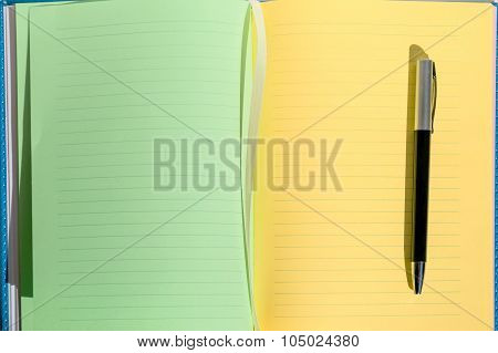 green and yellow sheets of notebook, pen