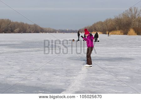 Young girl training new element of skating on a frozen river