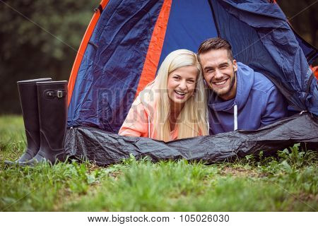 Happy couple lying in their tent in the countryside