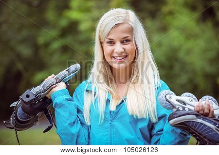 Happy blonde holding inline skates in the countryside