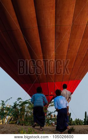 Asian Men standing in front of hot air balloon over Bagan