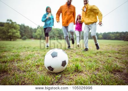 Friends running towards football in the countryside
