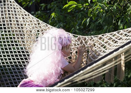 Little Girls In Brightly Colored Carnival Wigs In The Setting Sun In Summer In The Garden.