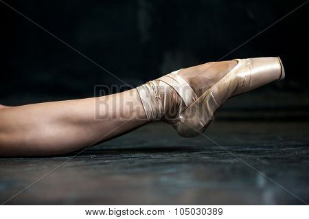 Close-up ballerina's leg in pointes on the black wooden floor