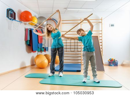 Happy, sports family, mother and son perform gymnastic exercises.