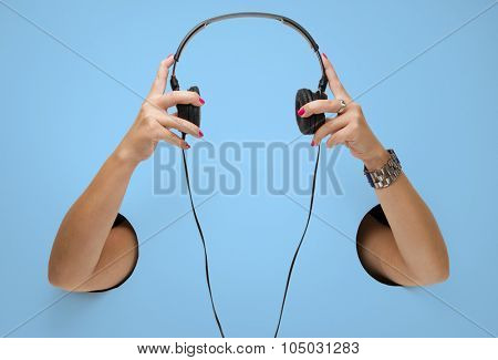 The headphones in a female hands through the holes
