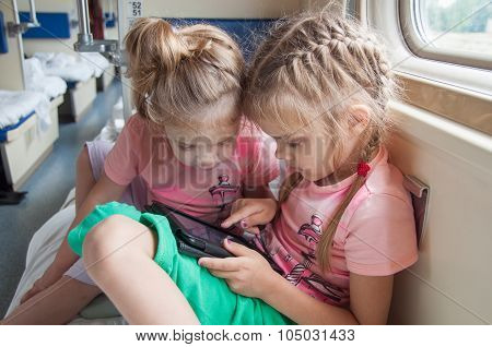 Two Girls Playing In The Second-class Tablet In A Train