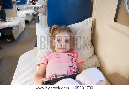 Frightened Girl Lying On The Bed With A Tablet In The Car With Reserved Seats