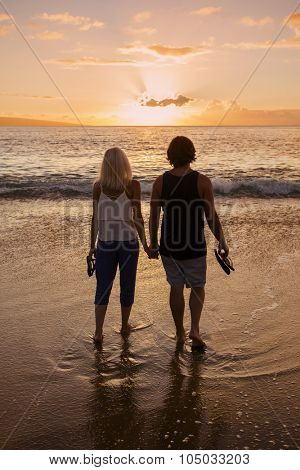 Couple in love and holding hands at the beach at sunset
