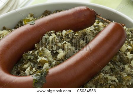Traditional dutch dish with stewed curly kale and smoked sausage close up