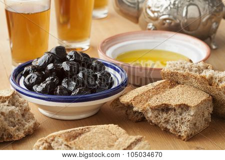 Moroccan traditional breakfast with olive oil,black olives,bread and tea