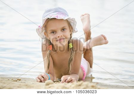Six Year Old Girl Lying On The Sand On The Beach
