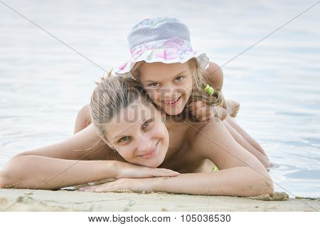 Happy Mother And Daughter On The Banks Of The River