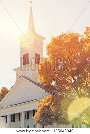 Traditional American white church in the fall with nautural sun flare