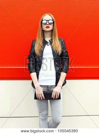 Fashion Pretty Woman Wearing A Rock Black Leather Jacket, Sunglasses And Handbag Clutch Over Red Bac