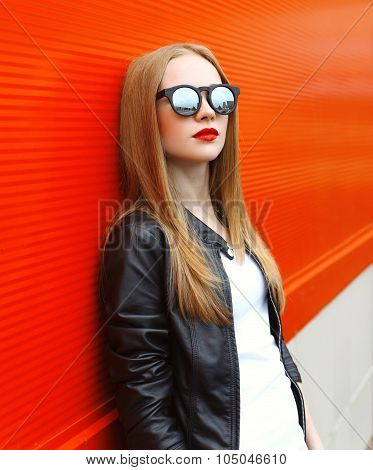 Fashion Stylish Woman Wearing A Rock Black Leather Jacket And Sunglasses With Red Lipstick In City
