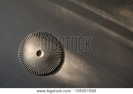 Round Ribbed Rosette On White Wall With Shadows
