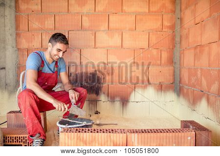 Construction Mason Worker, Bricklayer Building Brick Walls With Spatula And Mortar