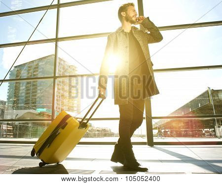 Traveling Man Walking And Talking On Mobile Phone At Airport