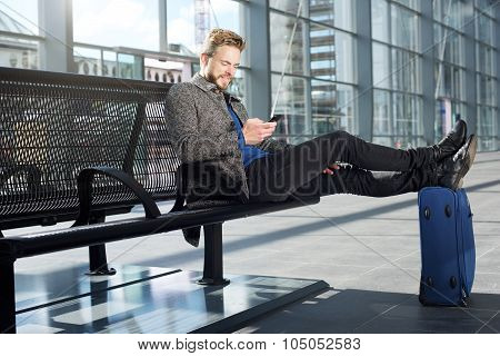 Handsome Man Relaxing At Airport With Mobile Phone