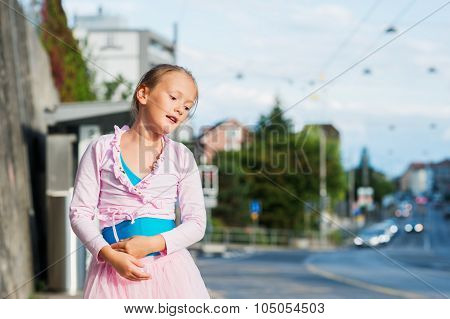 Cute little ballerina girl outdoors, wearing dance clothes, dancing in the street