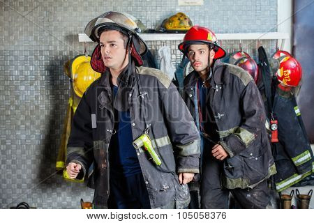 Young male firefighters in uniforms walking at fire station