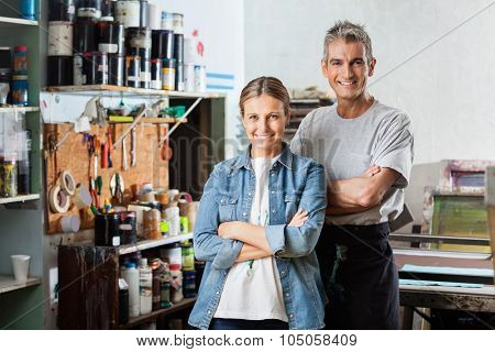 Portrait of smiling male and female workers standing arms crossed at stencil in paper factory