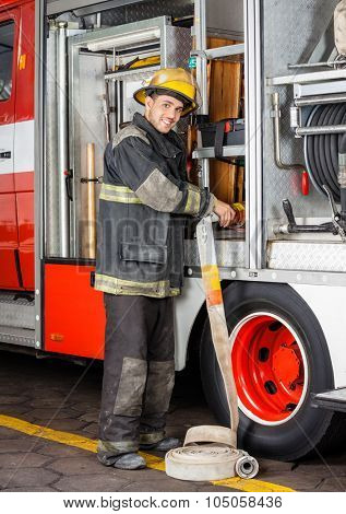 Portrait of smiling male firefighter adjusting hose in truck at fire station