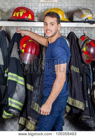 Side view portrait of confident fireman removing uniform hanging at fire station