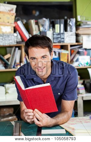 Portrait of confident male worker holding red cover book while leaning on table in factory