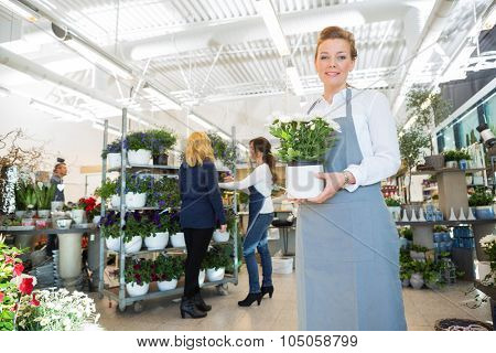Portrait of happy salesgirl holding flower pot with customer and colleague in background at shop