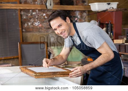 Portrait of confident mid adult male worker using tweezers to clean paper in factory