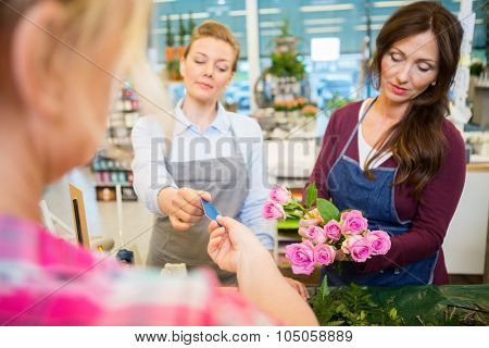 Florist accepting credit card from customer while colleague making rose bouquet at shop
