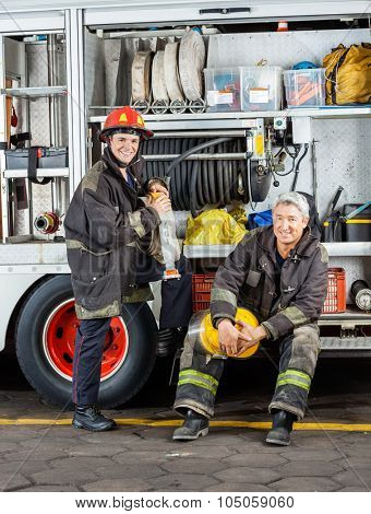 Portrait of happy male firefighters by truck at fire station