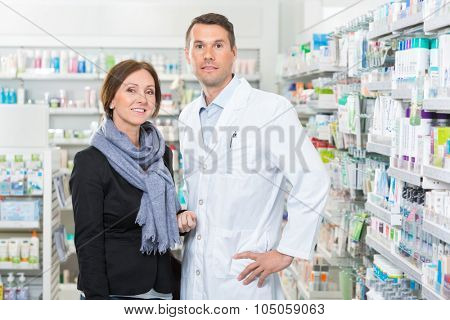 Portrait of confident pharmacist standing with customer in pharmacy