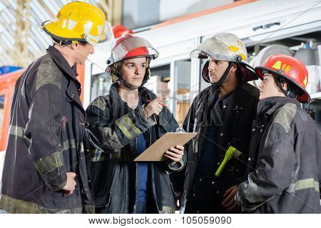 Male firefighter gesturing while discussing with colleagues at fire station