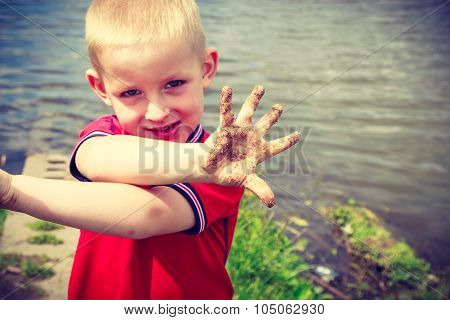 Child Playing Outdoor Showing Dirty Muddy Hands.